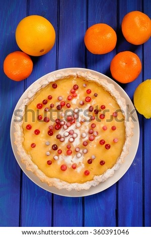 Homemade lemon pie decorated with fresh cranberries and icing sugar, whole clementines on deep blue table topview - stock photo