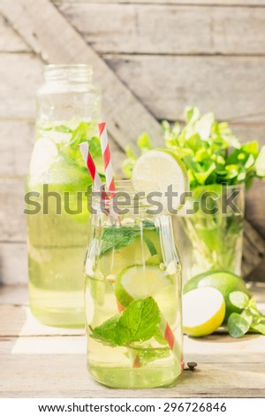Homemade lemonade in glass jars on wooden background. Toned image in Rural style - stock photo