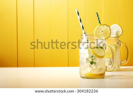 Homemade lemonade in mason jars with big green paper straw  - stock photo