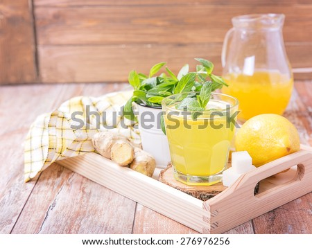 Homemade lemonade with lemon, ginger, mint on a wooden tray