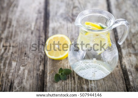 Homemade lemonade with lemons on a wooden table