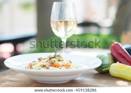 Homemade linguine pasta and a glass of white wine
