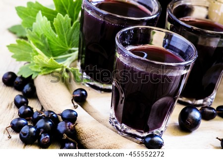 Homemade liqueur made from black currants and fresh berries, vintage wooden background, selective focus - stock photo