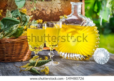 Homemade liqueur made of honey and lime in garden - stock photo