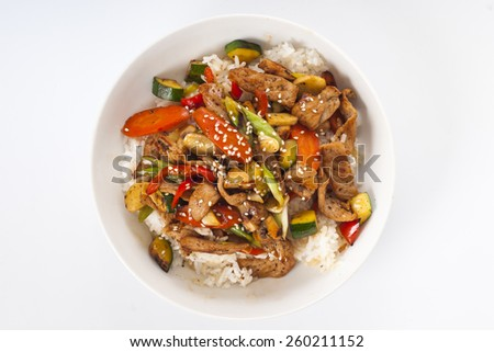 Homemade meal of Asian style pork and vegetable stir-fry on rice. - stock photo