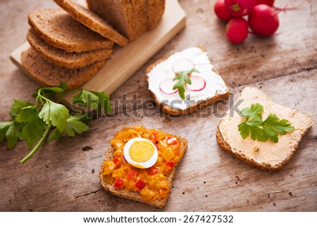 Homemade meal with bread and vegetarian spread on wooden background - stock photo