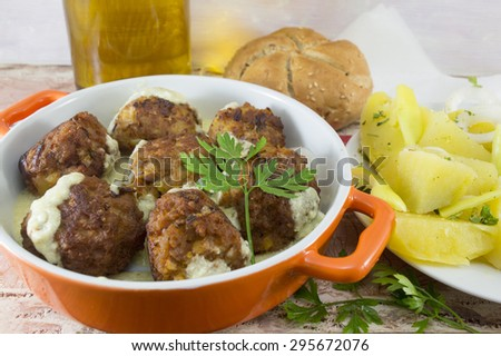Homemade meatballs served in an orange bowl with corn bread cooked potatoes and olive oil