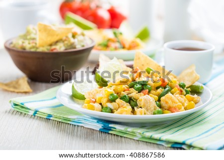 Homemade mexican salad scrambled egg served with corn tortilla chips and guacamole, healthy breakfast - stock photo