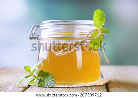 Homemade mint jelly in glass jar, on wooden table, on bright background - stock photo
