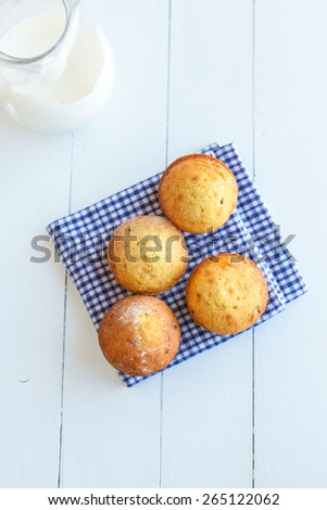 Homemade muffins in blue napkin and jug of milk on white wood table. Still life - stock photo