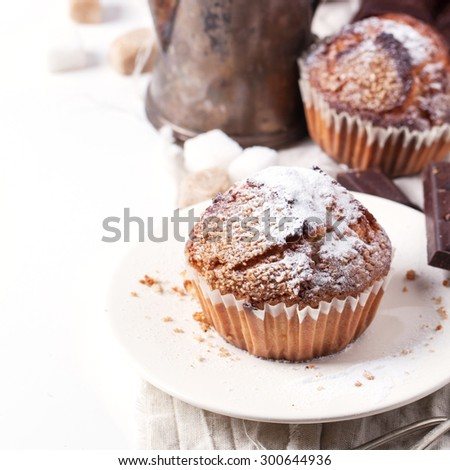 Homemade muffins with powdered sugar and vintage teapot over white. Square image with selective focus - stock photo