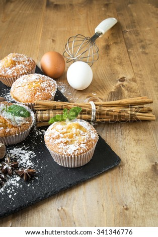 Homemade muffins with star anise, cinnamon and mint on old wooden table