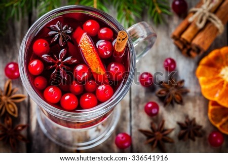 homemade mulled wine with orange slices, cranberries, cinnamon and anise on wooden table - stock photo