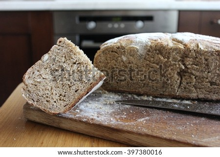 Homemade multigrain bread loaf and piece cut on the wooden board. French multigrain bread cut into pieces. Pieces of homemade french bread  on the wooden board. - stock photo