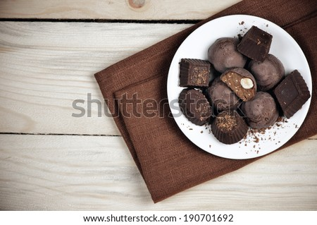 Homemade natural chocolate candy in plate on wooden background. - stock photo