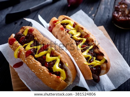 Homemade New York Style Hot dog. Sausage with sweet onion sauce, ketchup and mustard in white bun. wood background with onions, sauce and tongs on back - stock photo