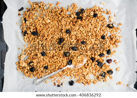Homemade oat, cherry and coconut granola over baking paper with spoon, top view - stock photo