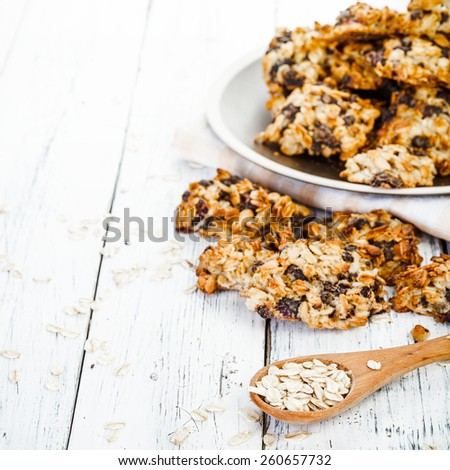 homemade oatmeal cookies on plate and spoon with oat on old white wooden table. FOCUS ON THE SPOON. - stock photo