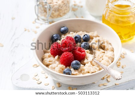 homemade oatmeal with berries for breakfast on white wooden board, closeup, horizontal