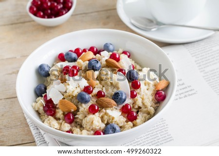 Homemade oatmeal with blueberries, almond and red currant for healthy breakfast.