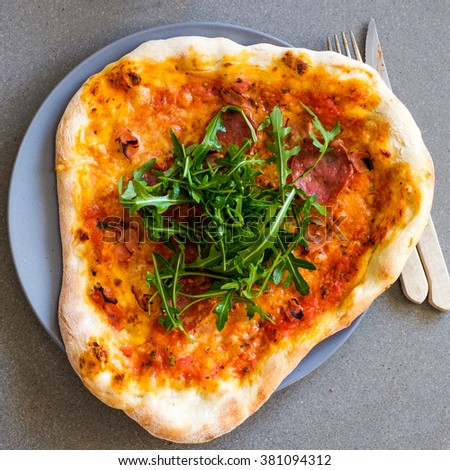 Homemade odd shape Pizza on a plate ready to be eaten - stock photo
