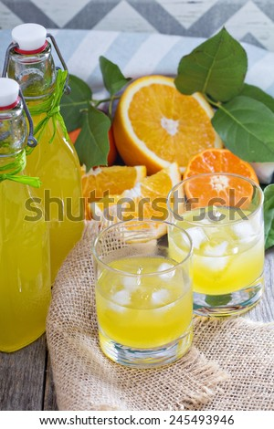 Homemade orange liqueur with fresh oranges on table - stock photo