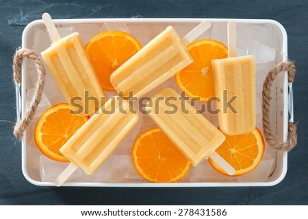 Homemade orange yogurt popsicles in an rustic ice filled tray with fresh fruit slices - stock photo