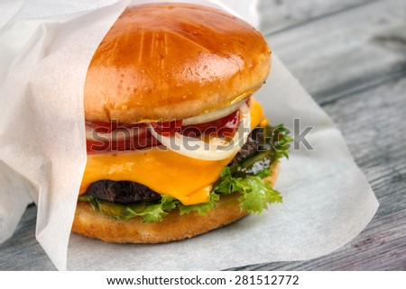 Homemade packed food , cheeseburger wrapped in paper on grey wooden surface - stock photo