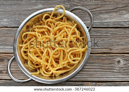 Homemade pasta in colander on wooden background  - stock photo