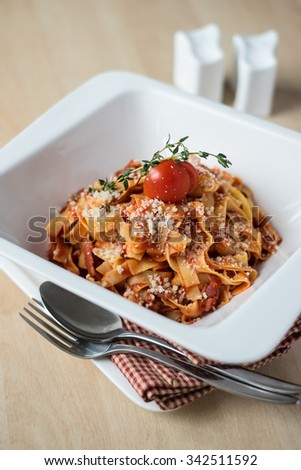 Homemade pasta tagliatelle with bolognese sauce from minced meat, carrot, celery, tomatoes, garnished with cherry tomato, thyme sprig and freshly grated parmesan cheese in a plate, selective focus - stock photo