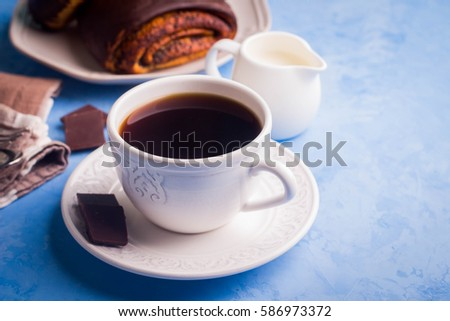 Homemade pastry with poppy seeds for breakfast icing chocolate on white plate with cup of coffee and milk on blue table background. copy space.