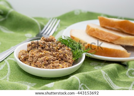 Homemade pate from a liver, carrots, garlic and eggs with dill on green table-cloth. White sliced bread on white plate