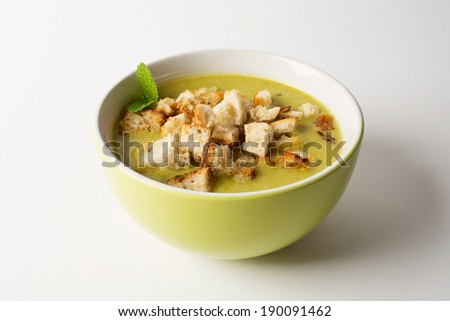 Homemade pea soup with croutons (on white) - stock photo
