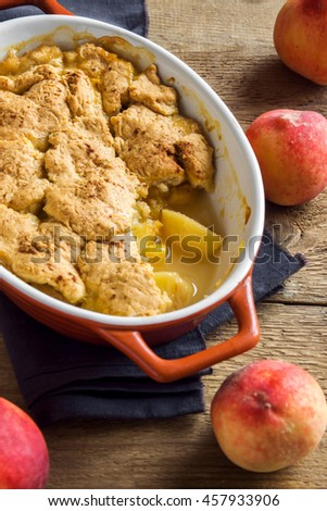 Homemade peach cobbler (crumble) in baking dish over rustic wooden background