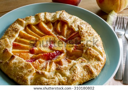 Homemade peach galette made with fresh organic peaches on blue plate with 2 folks and colorful napkin - stock photo