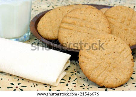 Homemade peanut butter cookies in a rustic tin plate with a glass of milk.
