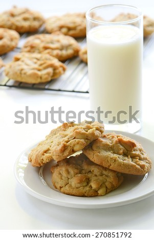Homemade peanut butter cookies with glass of milk and cookies cooling on rack in background - stock photo