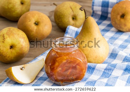 Homemade pear jam in jar on background fresh ripe pears  - stock photo