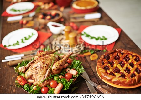 Homemade pie and roasted chicken on served Thanksgiving table - stock photo