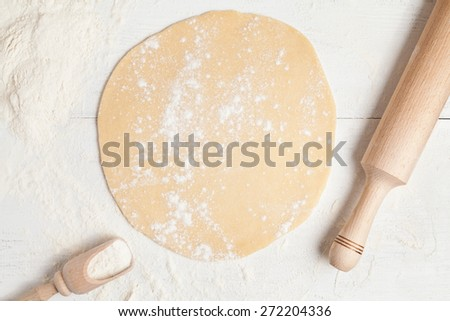 Homemade pie preparation recipe. Dough with rolling pin on white rustic kitchen table - stock photo