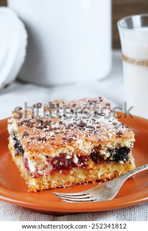 Homemade pie with jam and glass of milk on tablecloth background - stock photo