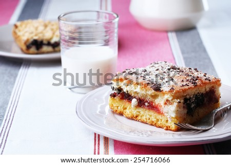 Homemade pies with jam and glass of milk on striped tablecloth background - stock photo