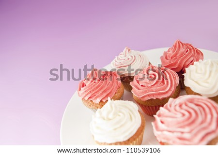 Homemade pink and white cupcakes on the white plate - stock photo
