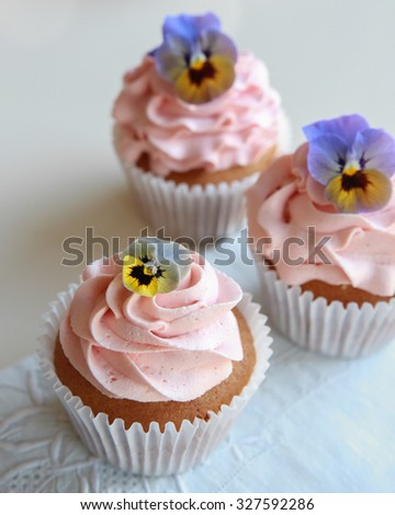 Homemade pink frosting vanilla cupcakes with edible flowers  - stock photo