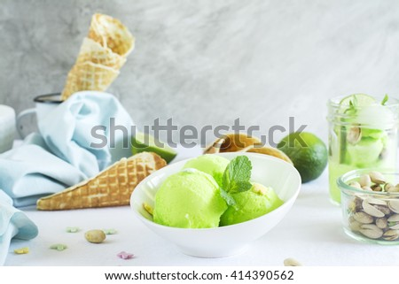 Homemade pistachio sorbet with lime, mint leaves, nuts and waffle cones. Selective focus - stock photo