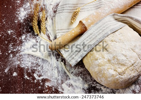 homemade pizza dough with rolling pin on a linen napkin on the wooden table - stock photo