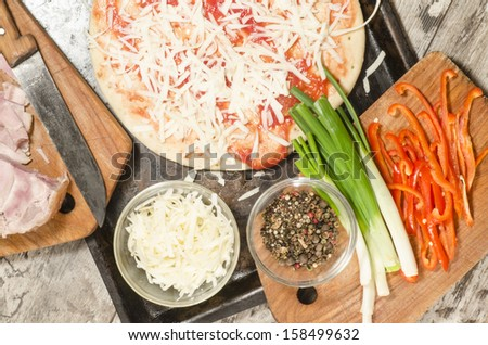 "Homemade pizza on baking tray and Ingredients for cooking. From the series ""Making homemade pizza"" - stock photo"