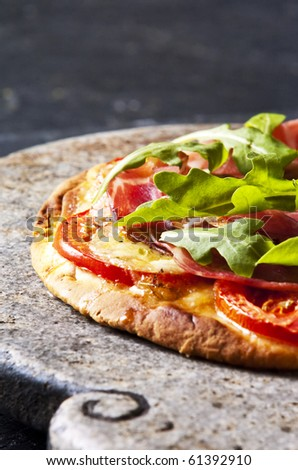 Homemade pizza served on a stone serving dish - stock photo