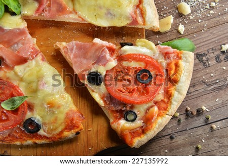 Homemade pizza with prosciutto, mozzarella, tomatoes and black olives - stock photo