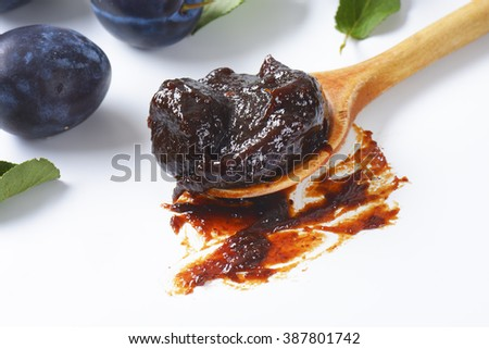 Homemade plum jam on a wooden spoon - stock photo